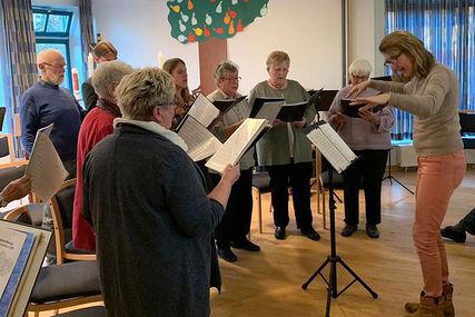 Rechts dirigiert die Chorleiterin Andrea van Bezouwen einige Mitglieder des Chors, die links stehen und singen.  - Copyright: Kirchengemeinde Siebeneichen