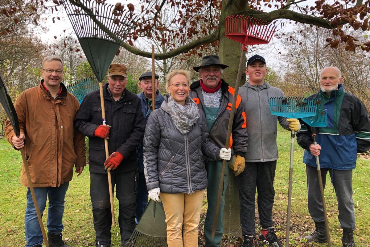 Eine Gruppe von freiwilligen Helfern mit Laubharken unter einem Baum